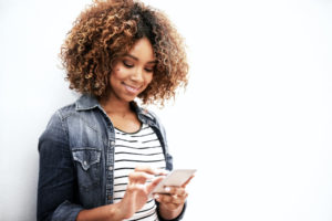 Cropped shot of a young woman using her cellphone against a white background